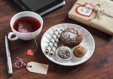 Tea cup with a homemade tea bag, sweets - cake, cookies and homemade candy, homemade Valentine's day gift in kraft paper and table Stock Photo