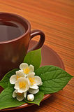 Tea cup with jasmine flower on the wood Royalty Free Stock Images