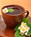 Tea cup with jasmine flower on the wood Stock Photos