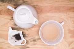 Tea cup and kettle. Flat lay - tea cup, tea kettle, small tray and used tea bag on wooden desk royalty free stock photography