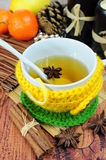 Tea in cup with knitted sleeve. Herbal tea in cup wrapped in knitted sleeve Royalty Free Stock Photos