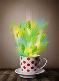 Tea cup with leaves and colorful abstract lights Royalty Free Stock Photos