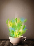 Tea cup with leaves and colorful abstract lights. Close up Royalty Free Stock Image