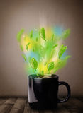 Tea cup with leaves and colorful abstract lights. Close up Royalty Free Stock Photography