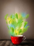 Tea cup with leaves and colorful abstract lights. Close up Royalty Free Stock Photo