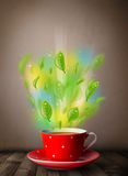 Tea cup with leaves and colorful abstract lights. Close up Royalty Free Stock Photos