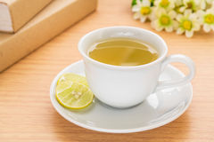Tea cup with lemon and book on table Royalty Free Stock Photos