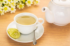 Tea cup with lemon and pot on table royalty free stock image