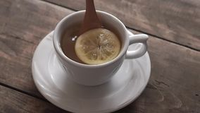 Tea cup with lemon on wooden table. From above stock video