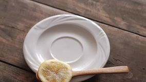 Tea cup with lemon on wooden table. From above stock footage