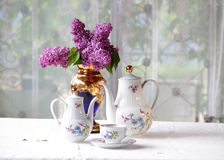 Tea in a cup, and a lilac bouquet on a table Royalty Free Stock Image