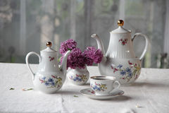 Tea in a cup, and a lilac bouquet on a table Stock Photo
