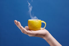 A tea cup made of lemon. Lemon cup in hand on a blue background. Creative composition on theme of natural fruit tea Stock Photos