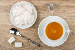 Tea in cup, meringue in saucer, sugar and teaspoon Royalty Free Stock Image