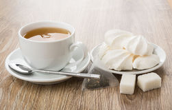 Tea in cup, meringue in saucer, tea bag, lumpy sugar Stock Photos