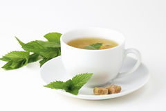 Tea cup with mint. A cup of mint tea with peppermint (mint) leaves and brown sugar on a white background stock photo