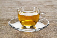 Tea cup over rough textile Royalty Free Stock Images