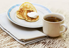 Tea cup and pancakes with cream on the plate. Breakfest set with tea cup and pancakes with cream on the plate Stock Photo
