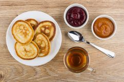 Tea in cup, pancakes, bowls with jam and teaspoon. Tea in cup, pancakes in plate, bowls with jam and teaspoon on wooden table. Top view Royalty Free Stock Images