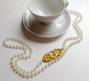 Tea Cup and Pearls. A vintage teacup and pretty pearls on white background Stock Photo