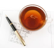 Tea cup and pen on plan Royalty Free Stock Photos
