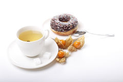 Tea cup and physalis with donut. Tea cup and physalis with chocolate donuts Royalty Free Stock Photos