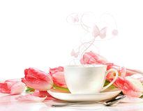 Tea cup with pink tulips on white royalty free stock image