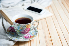 Tea cup placed on a wooden table with a smart phone, glasses, books. Copy space Royalty Free Stock Photo