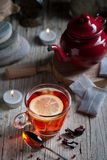 Glass with red tea on rustic wooden table. Tea cup with red porcelain teapot in rustic style Royalty Free Stock Photos