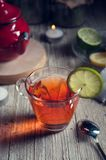 Glass with red tea on rustic wooden table. Tea cup with red porcelain teapot in rustic style Stock Photos