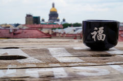 Tea Cup on the rough wooden table, on the background of St. Petersburg, in a rooftop cafe on a rainy day. Summer 2016. Stock Image