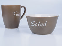 Tea cup and salad bowl isolated on white background Royalty Free Stock Image
