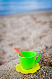 Tea cup upon the sand. Toy tea cup upon the sea sand against sea shore close-up Royalty Free Stock Photography