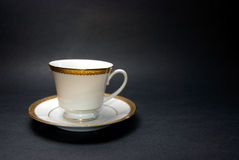 Tea Cup and Saucer. Fancy tea cup and saucer against black background Royalty Free Stock Image