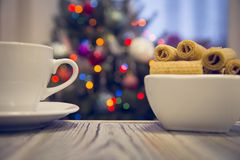 A tea cup and a bowl of cookies on a wooden table against decorated Christmas tree stock photos