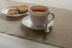 Tea Cup and saucer with cookies. Cup of black tea and biscuits on the table Stock Photos