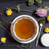 Tea in a cup and saucer, dried yellow roses, cake Stock Photography