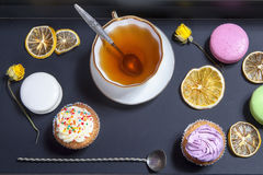 Tea in a cup and saucer, dried yellow roses, cake on a black background. royalty free stock photo
