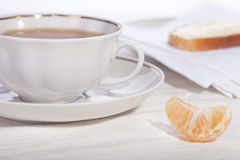 Tea cup on a saucer with a sandwich and a tangerin Stock Photo