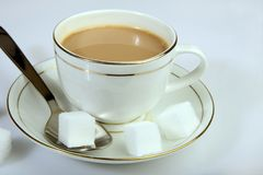 A tea cup and saucer with sugar cubes. And spoon, a morning table Stock Photo