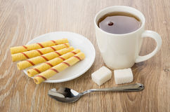Tea in cup, saucer with wafer rolls, teaspoon and sugar Stock Photo