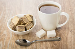 Tea in cup, saucer with waffle cubes, teaspoon and sugar Stock Photo
