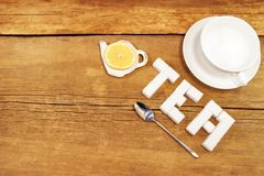 Tea cup and sign made from sugar on brown wooden table Royalty Free Stock Photos