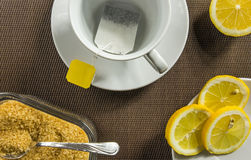 Tea cup, slices of lemon and brown sugar Royalty Free Stock Photo