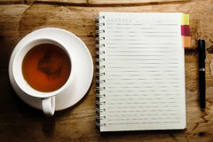 Tea cup, spiral notebook and pen Stock Image