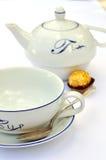 Tea cup, spoon, teapot Stock Photo