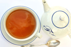 Tea cup, spoon and teapot Stock Images