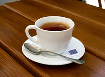 Tea, cup, spoon, wood, table. A cup of black tea on a wooden desk, and tsp royalty free stock photo