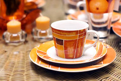 Tea cup. Spottily orange tea cup and candles stock image