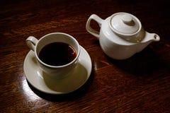 Tea cup and tea pot on table in dark room Stock Photos